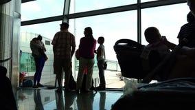 Passageiros pela janela no aeroporto que espera seu voo à aterrissagem em um de trajetória aérea video estoque