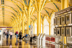 Passageiros que andam através de um aeroporto brilhante Imagem de Stock