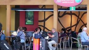 Passageiros que apreciam a refeição na padaria de Galiano e no restaurante do café filme