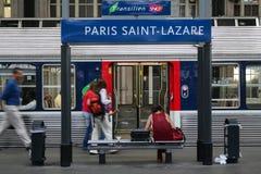 Passageiros que apressam-se perto de um trem suburbano em uma plataforma do estação de caminhos-de-ferro de Lazare de Saint de Ga imagens de stock royalty free