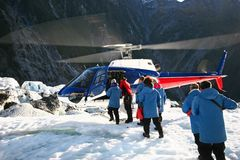 Passageiros que embarcam o helicóptero aterrado no gelo imagem de stock
