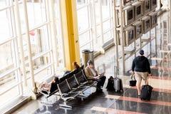 Passageiros que esperam na frente de uma janela interior brilhante do aeroporto Fotografia de Stock