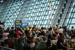 Passageiros que esperam na porta de partida aglomerada após o atraso, aeroporto de Shanghai Pudong, China imagens de stock royalty free