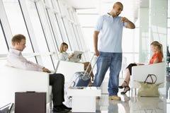 Passageiros que esperam na sala de estar da partida do aeroporto Fotos de Stock