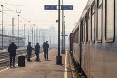 Passageiros que esperam para embarcar um trem na plataforma do estação de caminhos-de-ferro principal de Belgrado durante uma tar fotos de stock royalty free