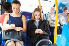 Passageiros que sentam-se no ônibus que envia mensagens de texto Fotos de Stock Royalty Free