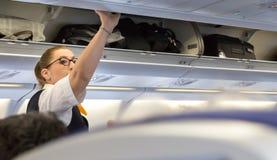 Passageiros que tomam sua bagagem do compartimento aéreo Fotografia de Stock Royalty Free