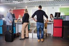 Passageiros que tornam mais pesada sua bagagem no aeroporto imagens de stock
