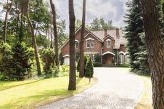 Passagem à residência inglesa do estilo na floresta com gras verdes imagens de stock royalty free