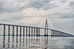 Passagem da estrada sobre a água no céu nebuloso Ponte sobre o mar em manaus, Brasil Conceito da arquitetura e de projeto Destino foto de stock