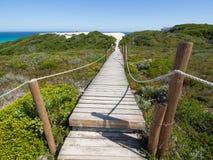 Passagem de madeira através das dunas verdes a um oceano de turquesa imagens de stock