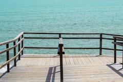Passagem de madeira com os trilhos que vão ao oceano fotografia de stock royalty free