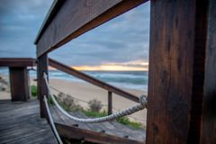 Passagem de madeira misteriosa da praia no por do sol fotos de stock royalty free