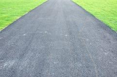 Passagem do asfalto ao longo do parque verde Imagens de Stock Royalty Free