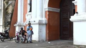 A passagem dos povos por mendigos deficientes implora no portal da igreja vídeos de arquivo
