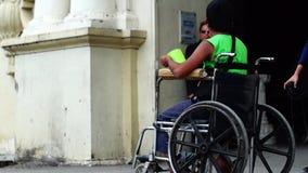 A passagem dos povos por um menino do paraplégico dos enfermos implorar quando em sua cadeira de rodas video estoque
