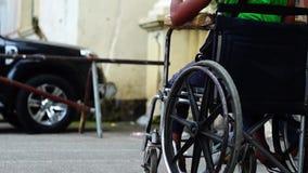 A passagem dos povos por um menino do paraplégico dos enfermos implorar quando em sua cadeira de rodas filme