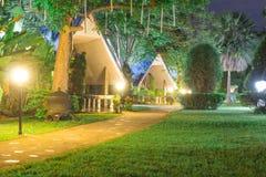 A passagem e o gramado do recurso na noite, com o claro alaranjado imagem de stock
