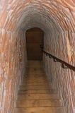 Passagem estreita feita dos tijolos com as escadas dentro das paredes do castelo medieval de Ammersoyen imagens de stock