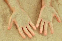 Passagens da areia através das mãos de uma criança imagem de stock