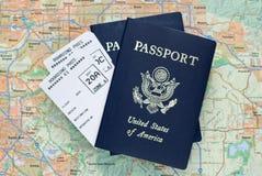Passagens de embarque do avião, passaportes americanos, mapa Imagem de Stock Royalty Free