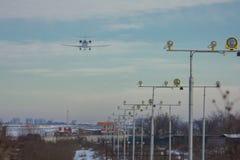 Passagens do avião de passageiros do passageiro sobre as luzes de aterrissagem e aterrissagem no aeroporto imagem de stock