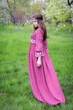 Passagens do modelo através da cidade a pé Moça com cabelo longo no vestido vermelho longo bonito com laço Foto de Stock