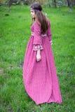 Passagens do modelo através da cidade a pé Moça com cabelo longo no vestido vermelho longo bonito com laço Foto de Stock Royalty Free