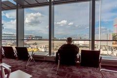 Passager dans l'aéroport se reposant dans le fauteuil et regardant dans la fenêtre Photographie stock