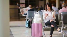Passager de ligne aérienne dans un avion de attente de vol de salon d'aéroport Femme caucasienne recherchant le temps dans la sal banque de vidéos