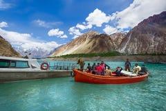 Passager et travailleur au lac d'attabad Photo stock