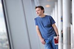 Passager masculin tenant le passeport et la carte d'embarquement à l'aéroport Photo stock