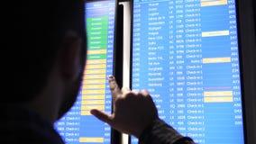 Passager regardant le panneau d'écran d'horaire et se dirigeant avec un doigt recherchant le bon vol clips vidéos