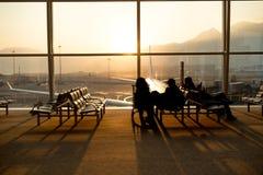 Passager s'asseyant dans un vol de attente d'aéroport de lobby dans le silho Photo stock
