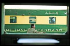 Passager s'asseyant sur un banc et un train de attente Photos libres de droits