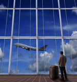 Passager se tenant avec la grande valise dans l'aéroport et regardant à a Image libre de droits