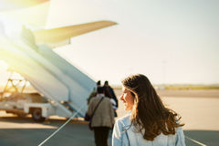 Passager walking from the airport terminal to the airplane for departure. Woman tourist passager getting in to airplane at airport, walking from the terminal to royalty free stock image