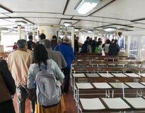 Passagerare får av en färja i Hong Kong Arkivfoton