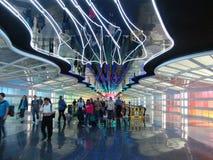 Passagerare går till och med den underjordiska gångbanan på en upptagen terminal, Arkivbild