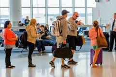 Passagerare köade i linjen för att stiga ombord på avvikelseporten Arkivfoto