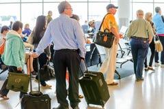 Passagerare köade i linjen för att stiga ombord på avvikelseporten Royaltyfri Bild