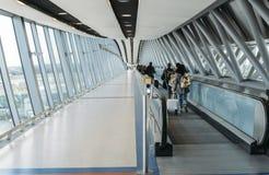 Passagerare med bagage går på en lång horisontalrulltrappa som täckas av en modern tunnel på norden för London Gatwick ` s Royaltyfria Bilder