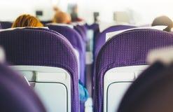 Passagerare sitter i de blåa fåtöljerna av flygplanet under flyget, sikten från baksidan av turister som flyger in i royaltyfri bild