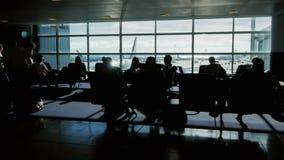 Passagerare sitter i ett väntande flygplanflyg Folket går förbi, ser konturerna arkivfilmer