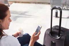 Passagerare som använder den mobila internet eller wifi i flygplats arkivbild
