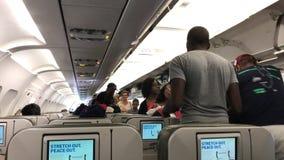 Passagerare som finner deras platser i ett flygplan stock video