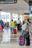 Passagerare som går med bagage i en flygplats Royaltyfria Bilder