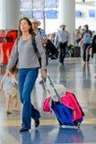 Passagerare som går med bagage i en flygplats Arkivfoto