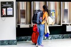 Passagerare som går med bagage i en flygplats Arkivbild