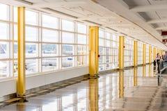 Passagerare som går till och med en ljus flygplats Royaltyfri Bild